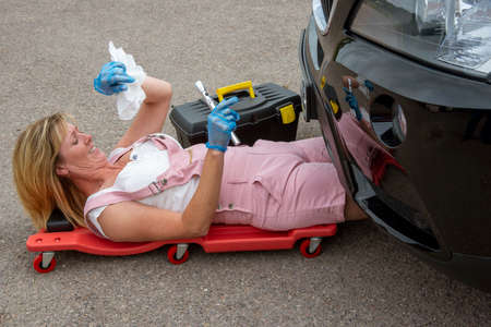 England, UK, circa 2014.  A woman mechanic laying on a crawler to access the underside of a car. Archivio Fotografico