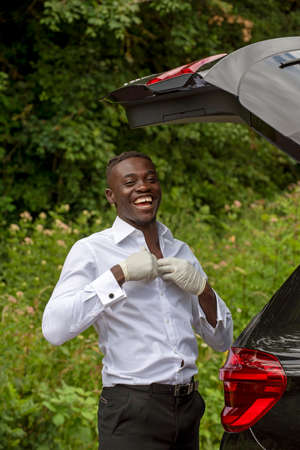 England, UK. 2020. Car driver with the boot open seen changing his clothes