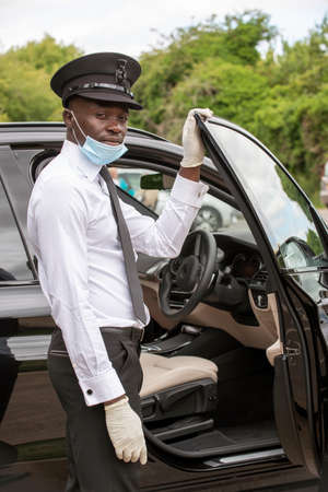 Hampshire, England, UK. 2020. A chauffeur entering his black car wearing a face mask and protective rubber gloves during the Covid-19 outbreak, Zdjęcie Seryjne