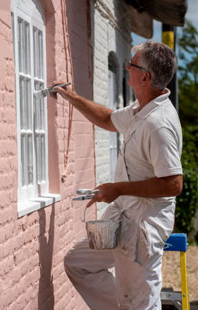 Hampshire, England, UK. 2020. Painter decorator painting small windows on a rural house