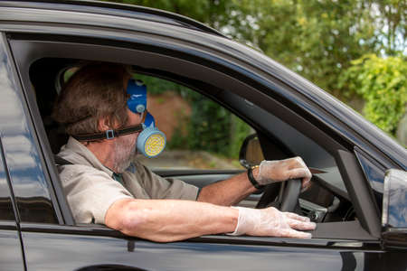 Hampshire, England, UK. 2020. Car driver wearing medical protective equipmment, mask, goggles and gloves during Covid-19 outbreak,