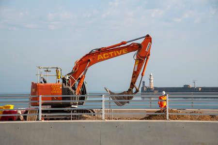 Dover, Kent, England, UK. 2020.  Civil engineering work being carried out at Dover Harbour using a excavator with a backdrop of the harbour entrance.