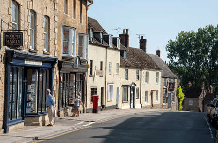 Malmesbury, Wiltshire, England, UK. 2020.  People viewing an estate agents window on the High Street in Malmesbury a desirable location to live,