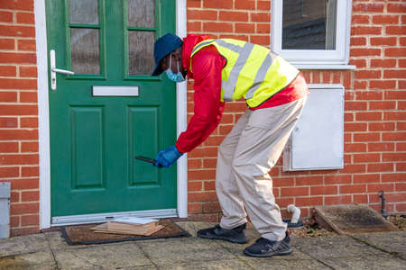 Hampshire, England, UK. 2020, Male courier delivering parcels and packages during Covid-19 epidemic wearing gloves and a mask. Recording on mobile phone the delivery.