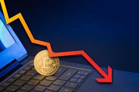 bitcoin standing upright on laptop keyboard with arrow pointing down