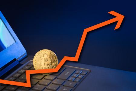 Bitcoin rechtop op laptop toetsenbord met pijl omhoog Stockfoto