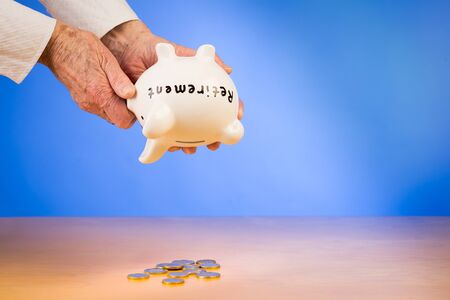 Elderly woman empties her piggybank  with savings from her retirement with space for text Stock Photo