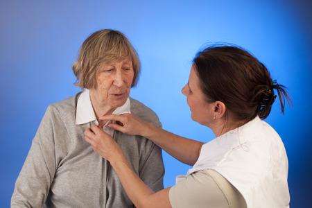 nurse helps a senior woman with dressing in a homecare situation Reklamní fotografie