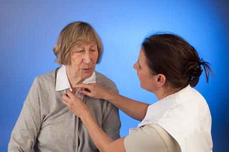 verpleegster helpt een oudere vrouw met verkleden in een thuiszorgsituatie Stockfoto