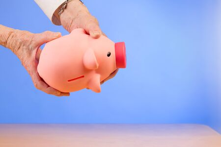 piggybank: senior woman empties a piggybank and nothing comes out