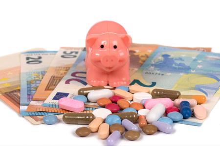 multicolored pills and  a piggybank on some banknotes isolated on  a white background