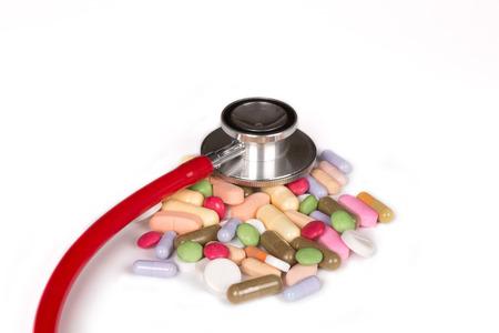 sommige veelkleurige pillen en een stethoscoop geïsoleerd op een witte achtergrond