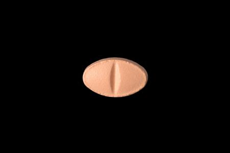 close-up van een zalm roze pil geïsoleerd op een zwarte achtergrond.psd