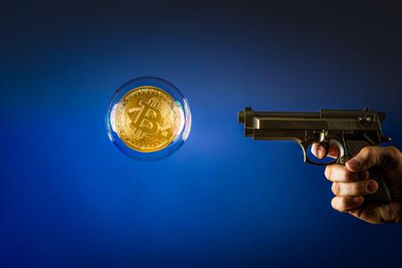 bitcoin bubble en een pistool gericht op de bitcoin bubble Stockfoto