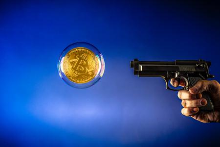 bitcoin in een bubbel en pistool gericht op de bitcoin Stockfoto