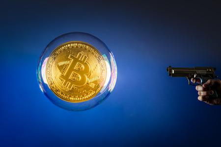 een pistool wijzend op een enorme bitcoin in een bubbel Stockfoto