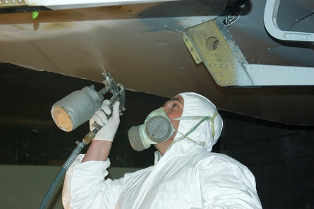 Tradesman sprays primer coat on the underside of a wing on a Dornier 228 aircraft