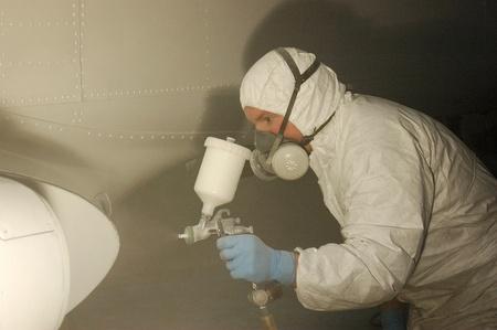Tradesman sprays the fuselage on a Dornier 228 aircraft Reklamní fotografie - 15108553