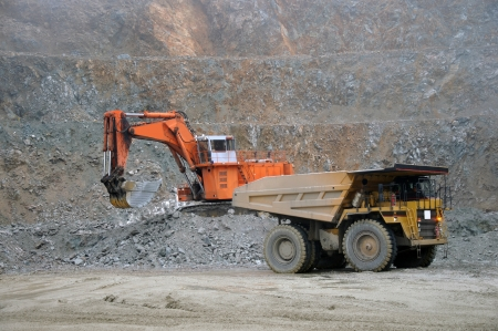 open pit: Digger loading up trucks with rock at Stockton Coal Mine, Westland, New Zealand Stock Photo