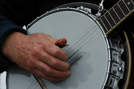 closeup of persons hands playing a banjo