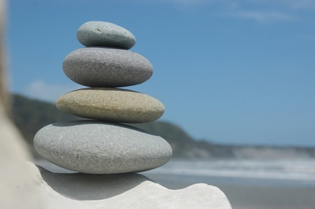 stacked up: smooth rocks stacked up with beach scene in background
