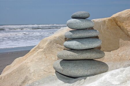 smooth rocks stacked up with beach scene in background photo