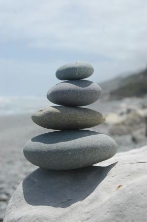 smooth rocks stacked up with beach scene in background Stock Photo - 15118113