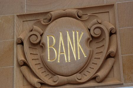 Ornate bank sign carved into snadstone