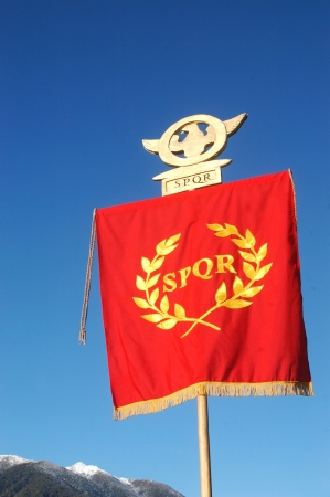 Roman Standard displaying SPQR, against blue sky and alps Stock Photo