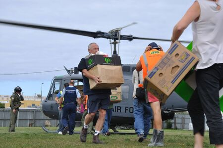 australasia: Volunteer relief workers scramble for food supplies from a New Zealand Air Force Iroquois helicopter after the 6.4 earthquake in Christchurch, South Island, New Zealand, 22-2-2011