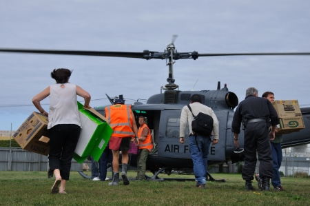 Volunteer relief workers scramble for food supplies from a New Zealand Air Force Iroquois helicopter after the 6.4 earthquake in Christchurch, South Island, New Zealand, 22-2-2011