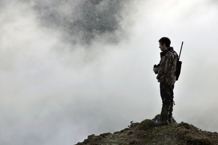 deer hunting: hunter looking for game animals such as chamois, deer or tahr, in  South Westlands Southern Alps, New Zealand