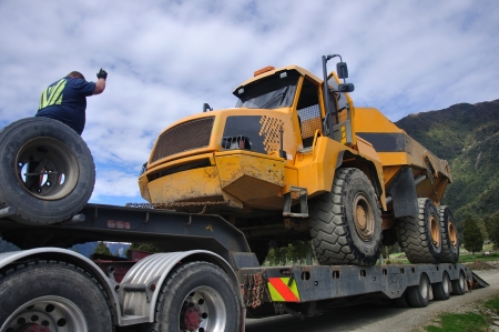 dumpster: a truck driver directs a 30 ton dumpster comes aboard his rig. Stock Photo