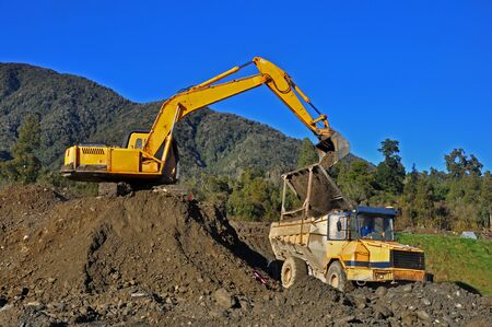 tipping: Excavator filling a dump truck at a construction site in Westland