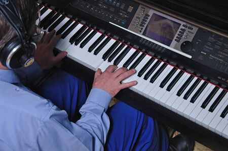 Detail of a man playing an electronic piano in a live performance photo