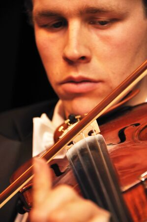 Detail of a man playing a violin in a live performance photo