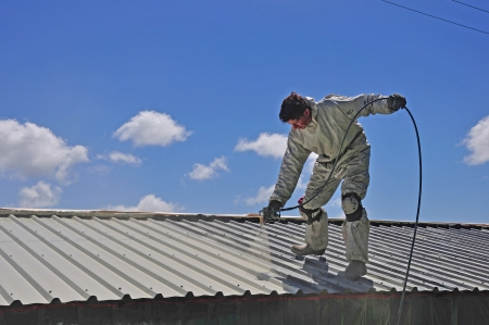 industrial machinery: A trademan uses an airless spray to paint the roof of a building Stock Photo