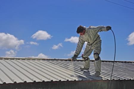 edificio industrial: Un trademan utiliza un pulverizador sin aire para pintar el techo de un edificio