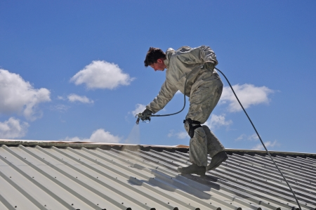 A trademan uses an airless spray to paint the roof of a building