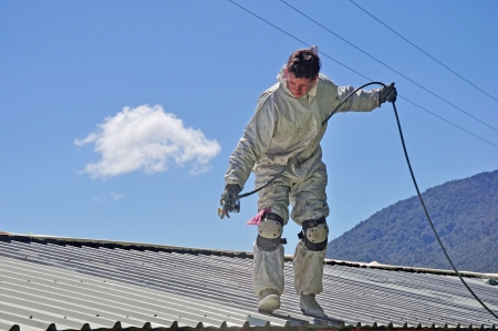 A trademan uses an airless spray to paint the roof of a building Stok Fotoğraf
