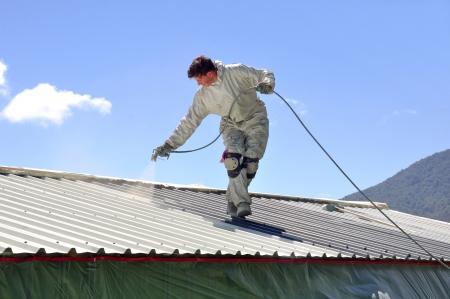 hombre pintando: Un trademan utiliza un pulverizador sin aire para pintar el techo de un edificio