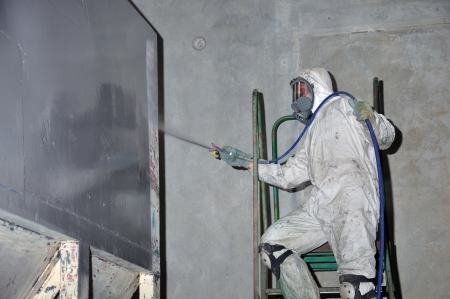 A trademan uses an airless spray to paint a coal hopper inside a manufacturing plant photo