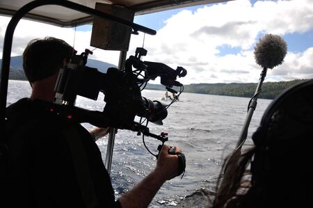 Cameraman and sound recordist at work on the lake photo