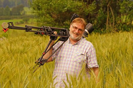 Cameraman at work in a wheat field photo