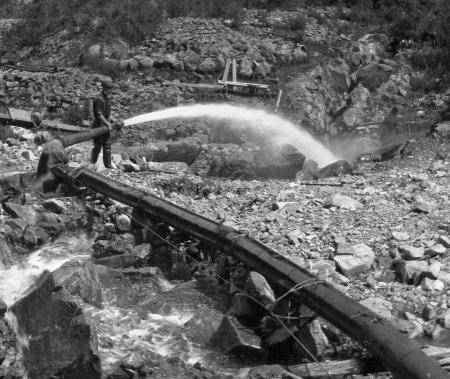 alluvial: Circa 1910  Sluice gun washing gravel bearing alluvial gold, New Zealand