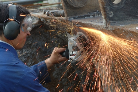 man wearing safety goggles grinds welding splatter off a machine