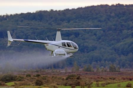 helicopter spraying fertiliser on a crop in Westland, New Zealand Stok Fotoğraf