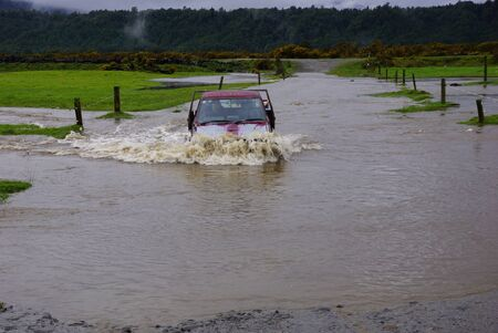 Farmer crosses a flooded creek in his ute, Westland, New Zealand photo