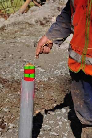 seismic: Man lowering an explosive charge into a three metre hole for a seismic reflective survey