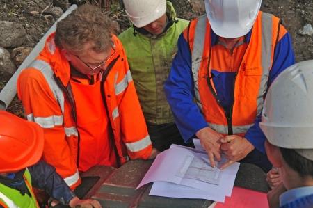 フィールドに地質学者は反射法地震探査の結果を話し合う